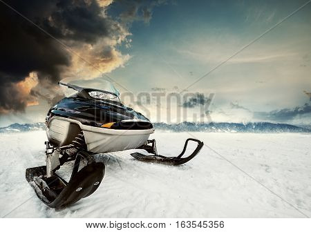 Snowmachine on the mountain lake frozen surface with thunderstorm clouds on the background