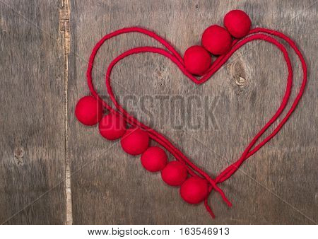 circuit of red heart and beads made of wool merino on the wooden background. Heart silhouette