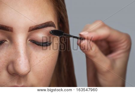 Master makeup corrects and gives shape to pull out with forceps previously painted with henna eyebrows in a beauty salon. Professional care for face.
