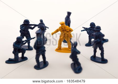 Blue toy soldiers surrounding a brown toy soldier
