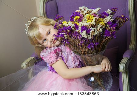 Little happy princess girl in pink dress and crown in her royal room sitting on chair and holding vase with flowers.