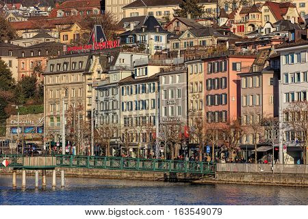 Zurich, Switzerland - 27 December, 2016: historic buildings along the Limmat river, people and Christmas illumination lamps temporarily installed for the Christmastime on the embankment of the river. Zurich is the largest city in Switzerland.