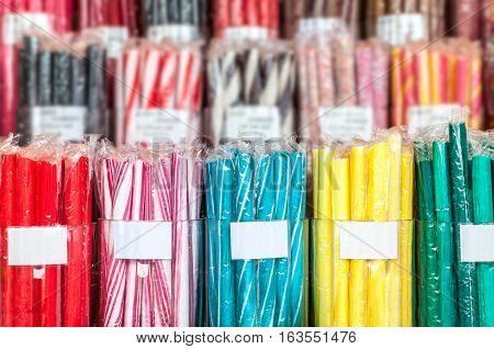 Bunches of candy sticks in different colors wrapped in plastic cellophane. Shallow depth of field, labels with copy space.