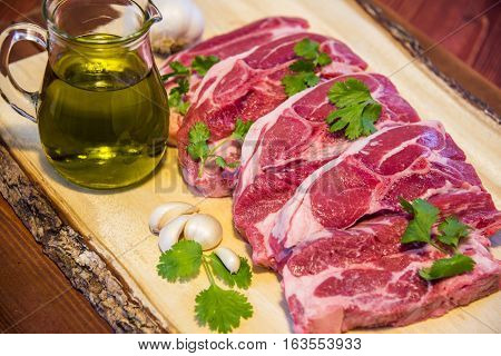 fresh beef meat, raw meat, raw steaks, raw beef streak, four steaks of fresh meat on wooden board, freshness of raw steaks with olive oil