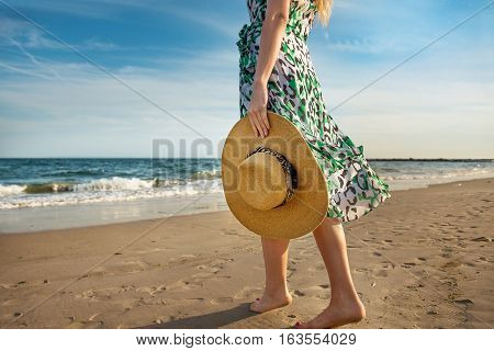 Barefoot woman walking on the ocean beach sand and enjoy the vacation during the tourist trip to the tropical island.