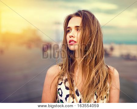 Beautiful girl enjoy the walk on the beach boardwalk at sunset time. Woman loking to the side outdoors.