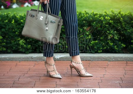 Businesswoman summer outfit for office. Fashionable woman wear high-hells shoes blue coton pants with white stripes and hold grey bag outdoors.