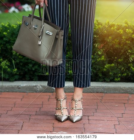 Women's legs in grey high heels shoes. Bright grey shoes bag and blue pants. Cotton pants stylish ladies shoes and bag. Businesswoman office clothes. Street fashion. Street style. Business casual look. Summer outfit.