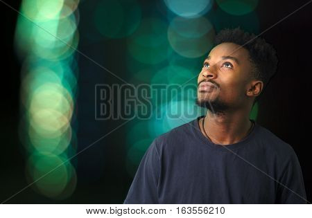 young man staring looking up green on illuminated background