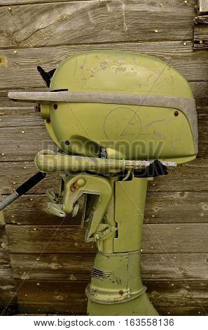 An old vintage green boat motor used for fishing and trolling leans again a weathered wooden fence