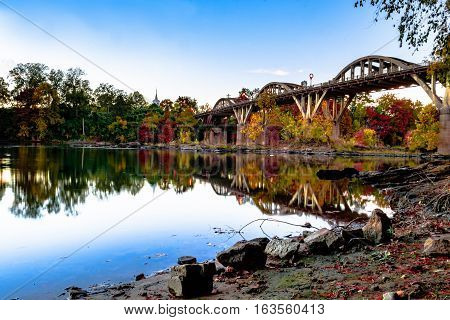 Wetumpka Alabama USA - November 20 2016: View of the Bibb Graves Bridge and fall folliage from the eastern shore of the Coosa River.