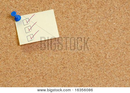check list on note thumb tack to corkboard