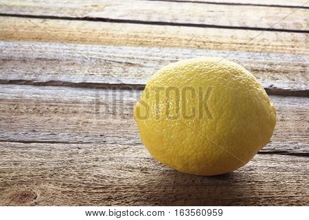 Fresh Whole Lemon on a Wooden Background