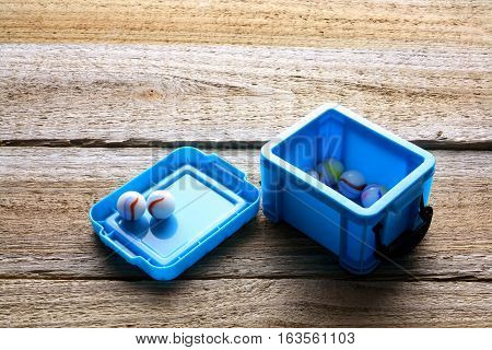 Marbles in Blue Box on Wooden Background