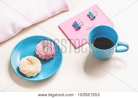 Small bright tasty cakes on plate near cup of dark coffee. Colour clerical clothespin are on rosy notebook