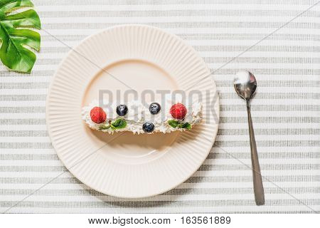 Sweet eclair with custard at white round porcelain utensil is beside dessert spoon. Tabby napkin under tasty food