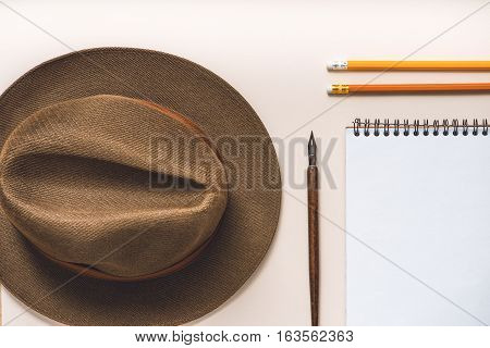 Fedora headwear near open notebook and pencils. Fountain pen is between them. Top view