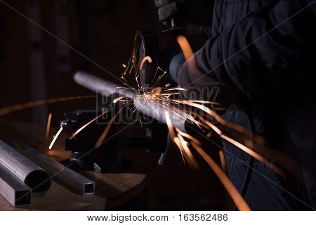 Steel worker in his workshop cutting a steel pipe that is held down by a clamp on a wood surface. As he cuts the steel pipe with a metal saw blade sharp sparks of fire appear but he is protected by his gloves and his thick work clothing. Blurry background