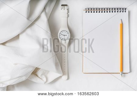 Elegant drapery material is beside clock and notepad with pencil. Top view