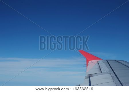 Red wing plane on blue skyview from the window of a plane of the blue sky background.
