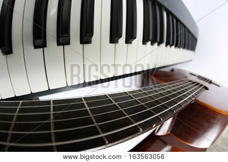 the piano keys and classical guitar close up on white background