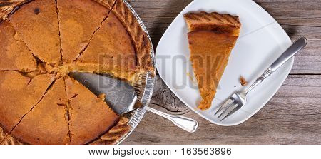 Overhead view of sliced pumpkin pie and spatula server on rustic table