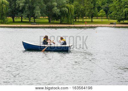 Rowing a small boat on The Serpentine, Hyde Park, England