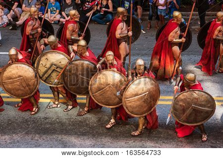 ATLANTA, GA - SEPTEMBER 2016:  Men dressed as Spartan warriors from the movie 300 strike a defensive pose with their shields and spears as they walk in the annual Dragon Con parade in Atlanta GA on September 3 2016.