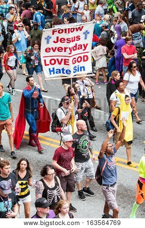 ATLANTA, GA - SEPTEMBER 2016:  A man carrying a religious sign uses a bullhorn to preach the gospel to a huge crowd of spectators and participants following the annual Dragon Con parade in Atlanta GA on September 3 2016.