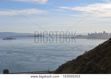 Looking down at the San Fransisco bay on a semi foggy day with the iconic bridge and skyline in the background