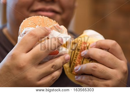 Close up of beef cheese burger in big hand.