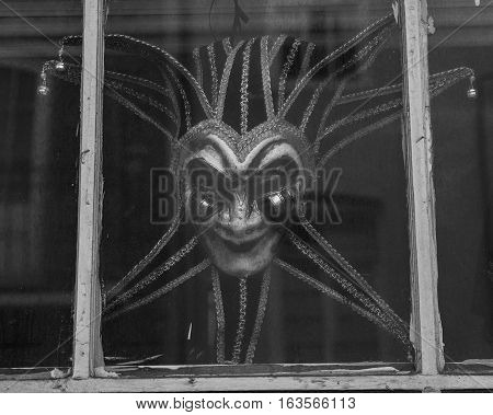 Black and White image of a Mardi Gra mask in the window - French Quarter of New Orleans Louisiana