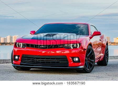December 31, 2016 - Port Orange, Florida. Shiny Red and Black Chevrolet Camaro SS parked along the river. This is the 6th Generation Chevy Camaro SS. The 5th Generation SS has a 6.2L V8 and began sales in 2015 for the 2016 model year.
