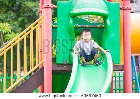 Little Asian Kid Playing Slide At The Playground