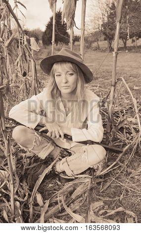 Beautiful woman sitting in corn field with a gun