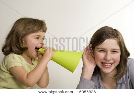 two girls using tube to communication