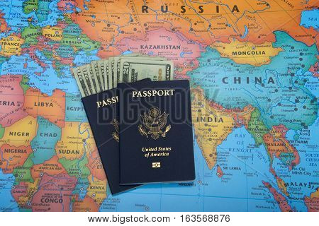 Alameda CA - December 31 2016: U.S. Passports with 20 dollar bills inside laying on a map of the world. Ready for travel and adventure.