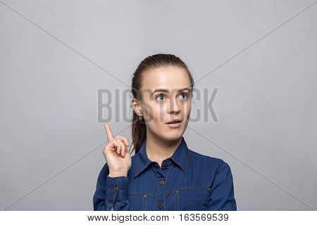 Portrait of puzzled woman with idea on gray background