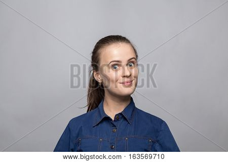 Portrait of pleased woman on gray background