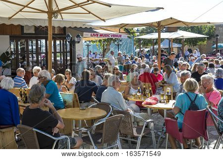 Aya Napa Greece - November 26 2016: Cyprus island senior tourists in a open air bar of the coubtry center