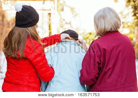 Photo of elderly woman helped by her carers