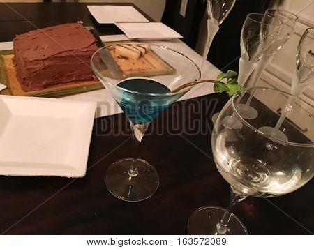 Blue Martini on wood table with slices of chocolate cake plates and wine glasses set up for party Conceptual photography high angle view