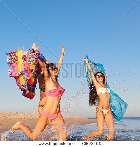Three beautiful young women in bathing suits and sunglasses fun jumping on the shore of the Red Sea waving colored fabrics