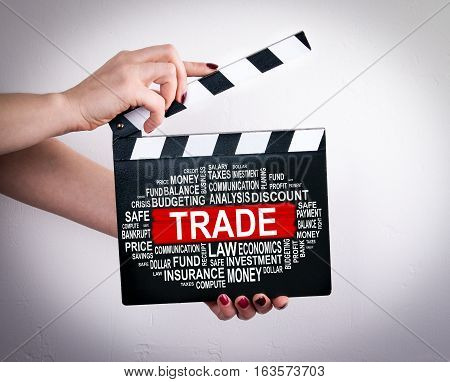 Trade Concept. Female hands holding movie clapper.