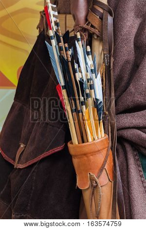Old set of historic wooden arrows with bright plumage in a leather quiver closeup