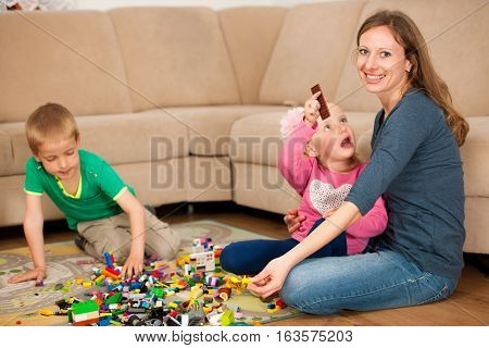 famili playing with toys on a flor in living room