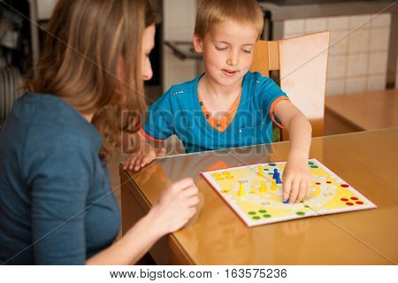 mom and kid playing ludo game in living room