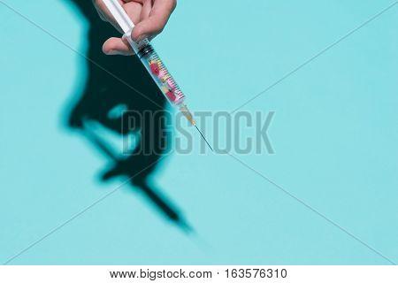 Hand Holding Yringe, Medical Injection With Medicine Pills Inside On Blue Background.