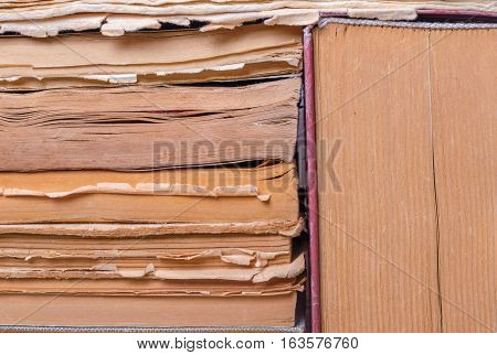 A stack of old books of different thickness, tattered pages