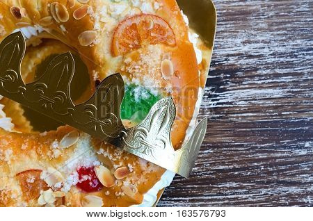 Roscon de reyes (kings' ring) typical dessert eaten in Spain to celebrate Epiphany or Dia de Reyes Magos (Three Kings' Day). Spanish Christmas cake with fruits nut and icing on wooden background